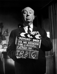 "Alfred Hitchcock on the ""Psycho"" set holding a clapboard"